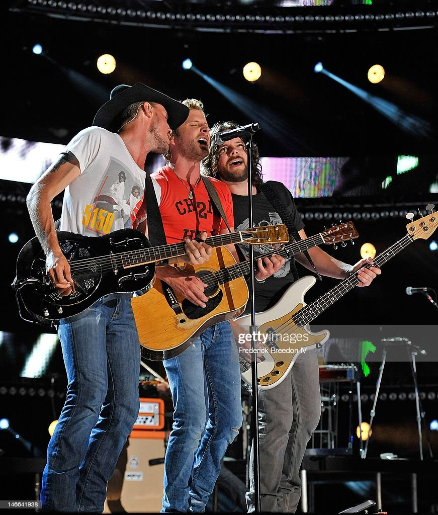 Brian Layson, Dierks Bentley, and Cassady Feasby perform on stage at LP Field during the 2012 CMA Music Festival on June 10, 2012 in Nashville, Tennessee.