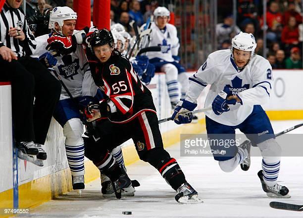Brian Lee of the Ottawa Senators pins Wayne Primeau of the Toronto Maple Leafs to the boards while teammate Christian Hanson of the Toronto Maple...