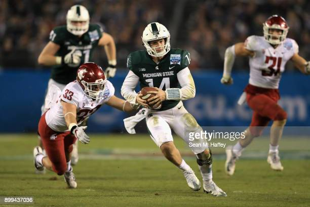 Brian Lewerke of the Michigan State Spartans eludes Dylan Hanser of the Washington State Cougars on a run play during the second half of the SDCCU...