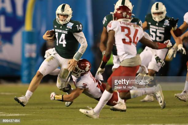 Brian Lewerke of the Michigan State Spartans eludes Isaac Dotson of the Washington State Cougars during the first half of the SDCCU Holiday Bowl at...