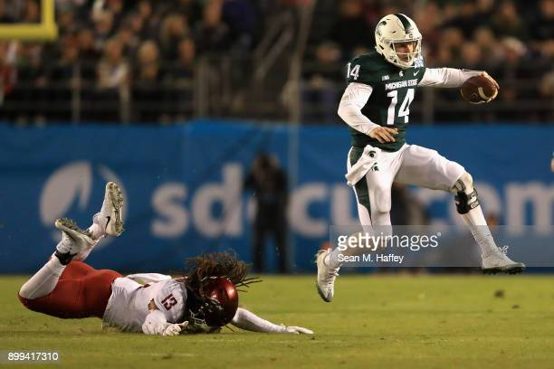 Brian Lewerke of the Michigan State Spartans eludes Jahad Woods of the Washington State Cougars during the first half of the SDCCU Holiday Bowl at...
