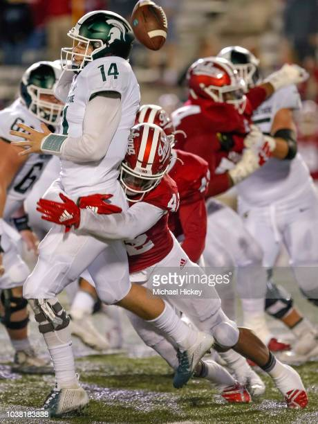 Brian Lewerke of the Michigan State Spartans fumbles the ball while throwing as Marcelino Ball of the Indiana Hoosiers makes the hit at Memorial...