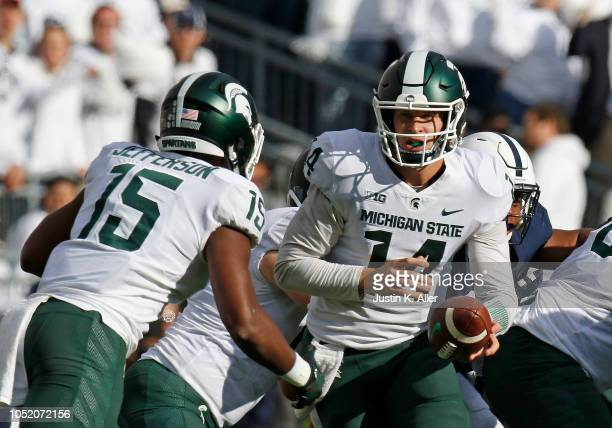 Brian Lewerke of the Michigan State Spartans hands off to La'Darius Jefferson of the Michigan State Spartans against the Penn State Nittany Lions on...