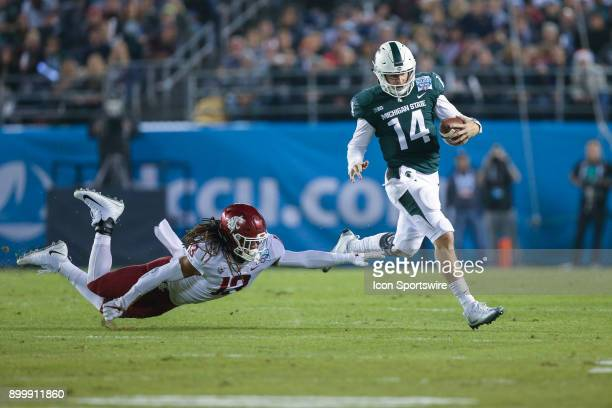 Brian Lewerke of the Michigan State Spartans runs for a gain in the game between the Washington State Cougars and the Michigan State Spartans on...