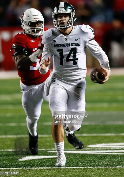 Brian Lewerke of the Michigan State Spartans runs from Kemoko Turay of the Rutgers Scarlet Knights during their game on November 25 2017 in...