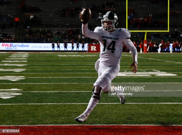 Brian Lewerke of the Michigan State Spartans runs in for a touchdown against the Rutgers Scarlet Knights during their game on November 25 2017 in...