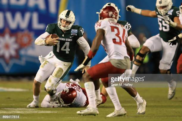 Brian Lewerke of the Michigan State Spartans runs past Isaac Dotson and Jalen Thompson of the Washington State Cougars during the first half of the...