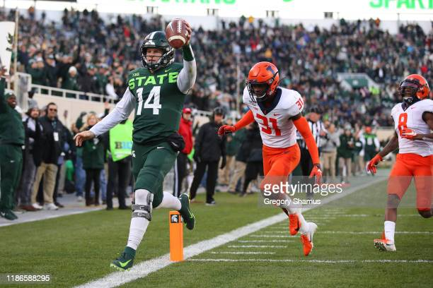 Brian Lewerke of the Michigan State Spartans scores a first quarter touchdown past Devon Witherspoon of the Illinois Fighting Illini at Spartan...