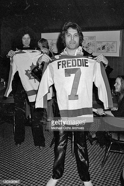 Brian May and Freddie Mercury of British rock band Queen receive ice hockey shirts whilst performing at the Montreal Forum, 26th January 1977....
