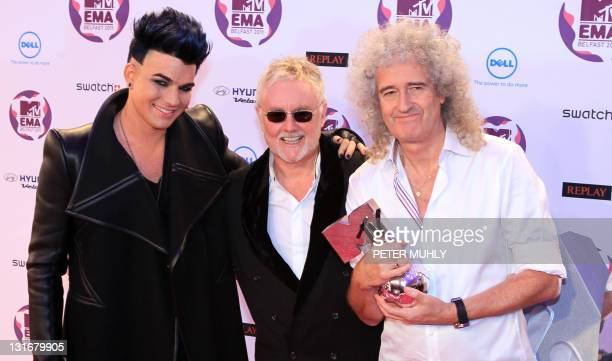 Brian May and Roger Taylor of the British rock band Queen pose with Adam Lambert and their Global Icon award at the MTV European Music Awards at the...