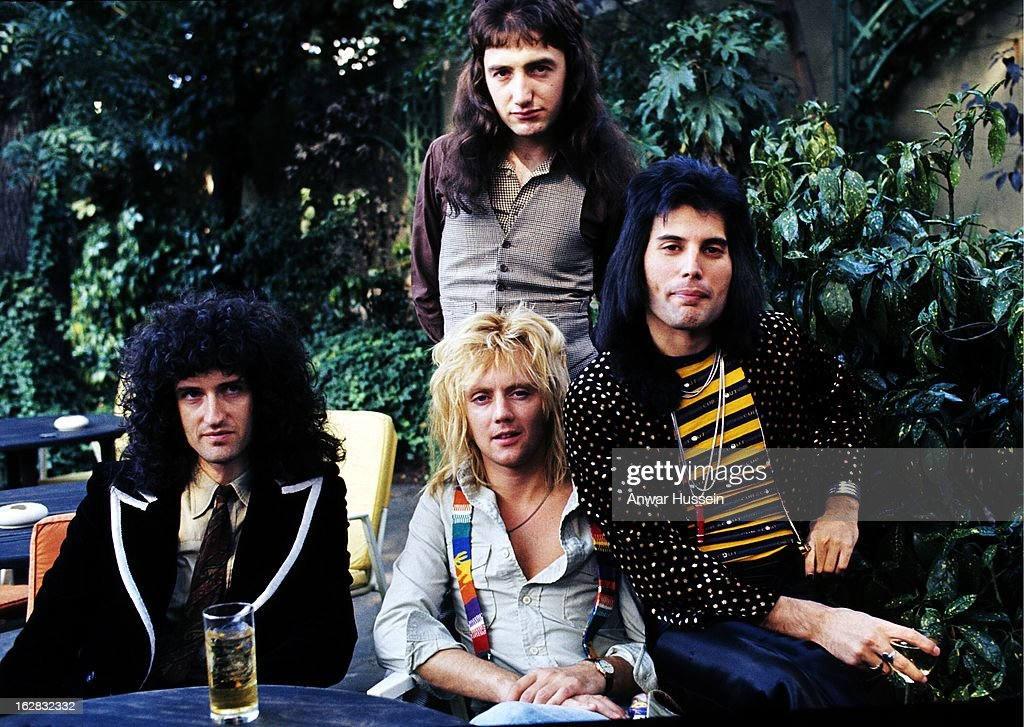 Brian May, John Deacon (standing), Roger Taylor and Freddie Mercury of British rock group Queen at Les Ambassadeurs where they were presented with silver, gold and platinum discs for sales in excess of one million of their hit single 'Bohemian Rhapsody', which was No 1 for 9 weeks on September 8, 1976 in London, England.