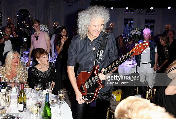 Brian May performs with the cast of 'We Will Rock You' during the second annual Freddie For A Day event in memory of Queen's late frontman Freddie...