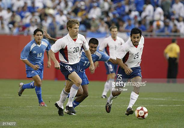 Brian McBride and Pablo Mastroeni of the USA hold off William Torres Alegria of El Salvador as they pursue the ball on July 12 2003 at Gillette...