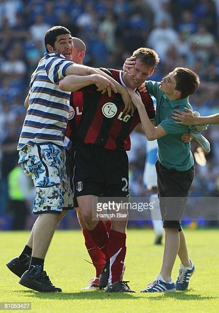 Brian McBride of Fulham is congratulated by fans after their team escapes relegation during the Barclays Premier League match between Portsmouth and...