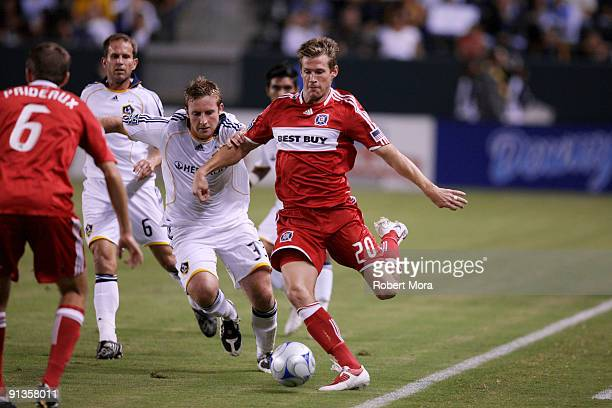 Brian McBride of the Chicago Fire controls the ball past Chris Birchall of the Los Angeles Galaxy during their MLS game at The Home Depot Center on...