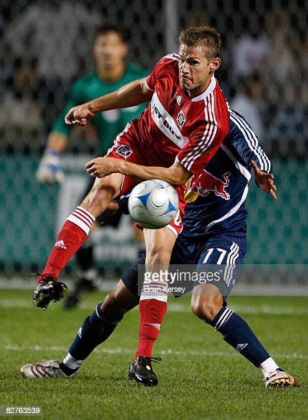 Brian McBride of the Chicago Fire kicks the ball away from Gabriel Cichero of the New York Red Bulls during the first half at Toyota Park on...
