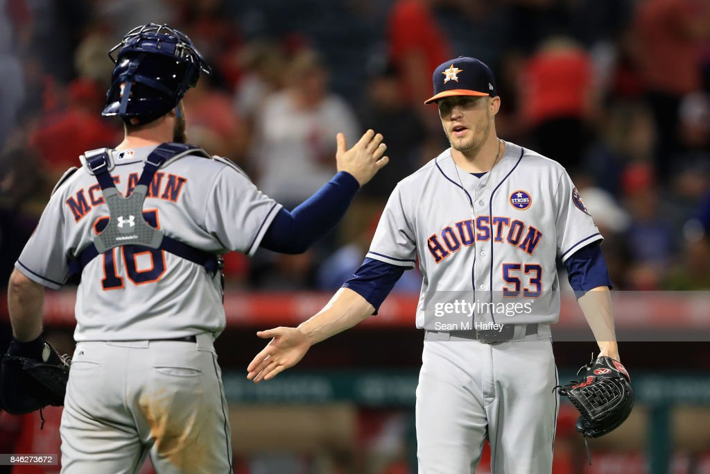 Brian McCann #16 and Ken Giles #53 of the Houston Astros celebrate defeating the Los Angeles Angels of Anaheim 1-0 in a game at Angel Stadium of Anaheim on September 12, 2017 in Anaheim, California.