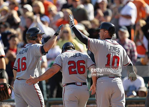 Brian McCann Dan Uggla and Chipper Jones of the Atlanta Braves celebrate after Uggla and Jones scored in the 10th inning against the San Francisco...