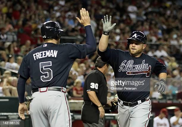 Brian McCann of the Atlanta Braves highfives Freddie Freeman after McCann hit a tworun home run against the Arizona Diamondbacks during the fifth...