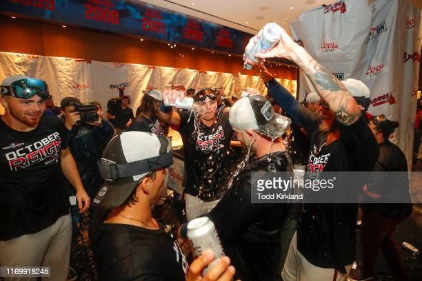 Brian McCann of the Atlanta Braves is showered with beer in the clubhouse at the conclusion of an MLB game against the San Francisco Giants in which...