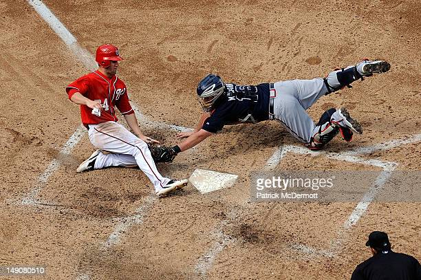 Brian McCann of the Atlanta Braves tags Bryce Harper of the Washington Nationals out at home plate in the sixth inning during a game at Nationals...