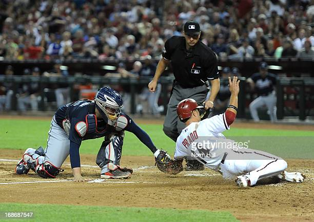 Brian McCann of the Atlanta Braves tags out Martin Prado of the Arizona Diamondbacks at home plate at Chase Field on May 13 2013 in Phoenix Arizona