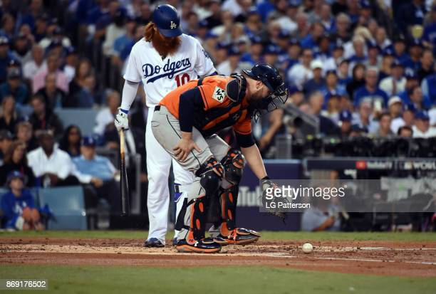 Brian McCann of the Houston Astros picks up the ball after Justin Turner of the Los Angeles Dodgers is hit by a pitch in the first inning of Game 7...
