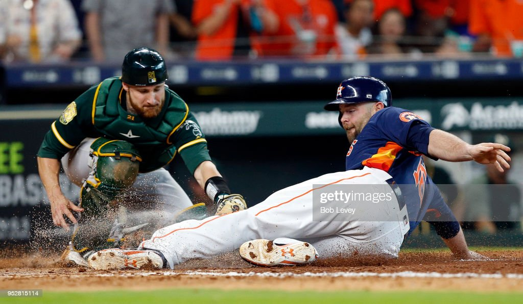 Brian McCann #16 of the Houston Astros scores in the seventh inning as he beats the tag attempt by Jonathan Lucroy #21 of the Oakland Athletics at Minute Maid Park on April 29, 2018 in Houston, Texas.