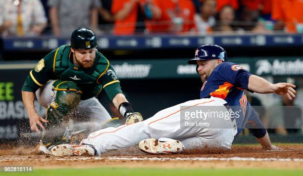 Brian McCann of the Houston Astros scores in the seventh inning as he beats the tag attempt by Jonathan Lucroy of the Oakland Athletics at Minute...
