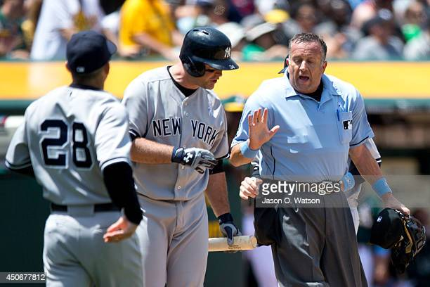 Brian McCann of the New York Yankees and manager Joe Girardi argue a called third strike with umpire Dale Scott during the fourth inning against the...
