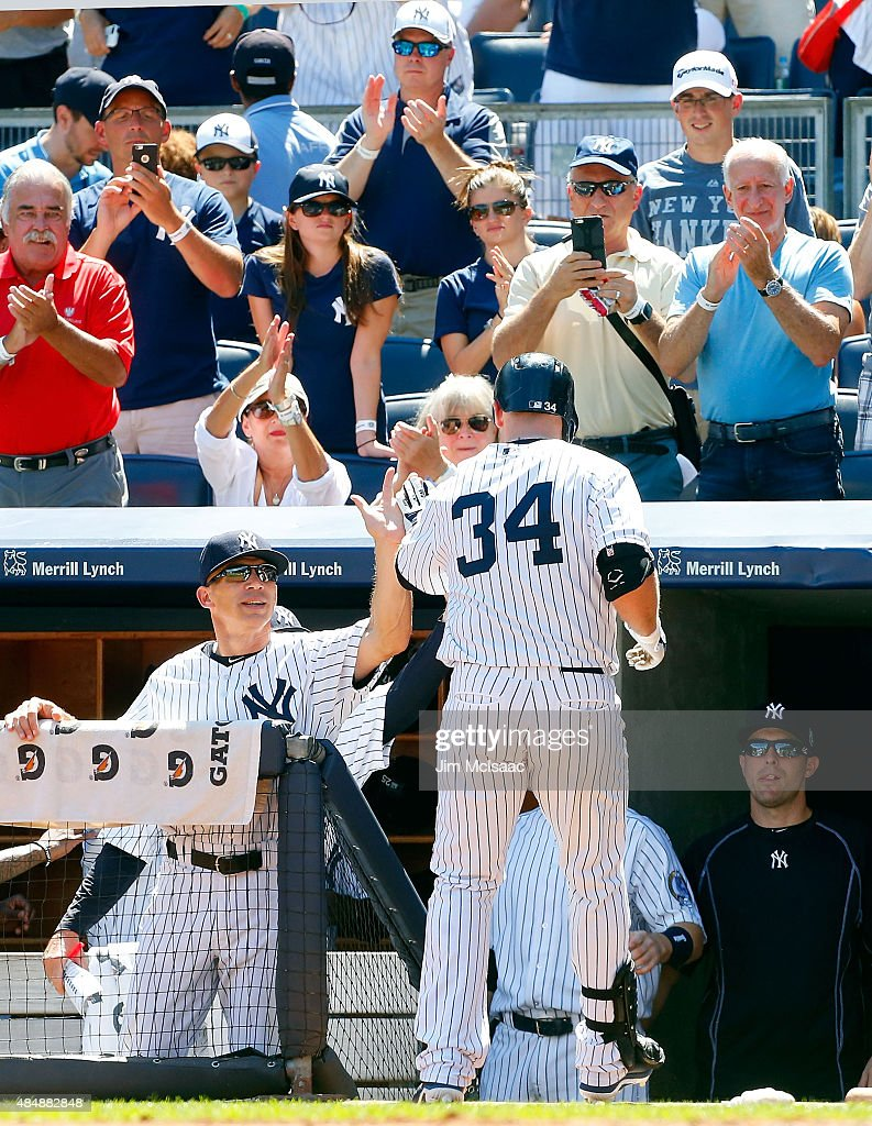 Brian McCann #34 of the New York Yankees celebrates his first inning home run against the Cleveland Indians with manager Joe Girardi #28 at Yankee Stadium on August 22, 2015 in the Bronx borough of New York City.