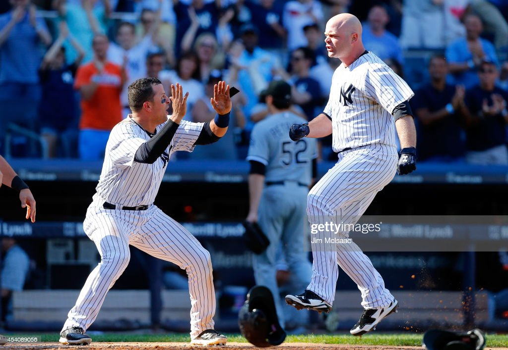 Brian McCann #34 of the New York Yankees celebrates his tenth inning game winning three run home run against Jake Petricka #52 of the Chicago White Sox with teammate Martin Prado #14 at Yankee Stadium on August 24, 2014 in the Bronx borough of New York City.