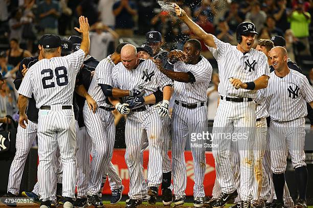 Brian McCann of the New York Yankees is mobbed by his teammates after connecting on a game winning three run home run in the twelfth inning against...