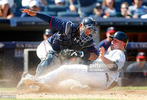 Brian McCann of the New York Yankees is tagged out at home by Kurt Suzuki of the Minnesota Twins trying to score on a fly ball in the eighth inning...