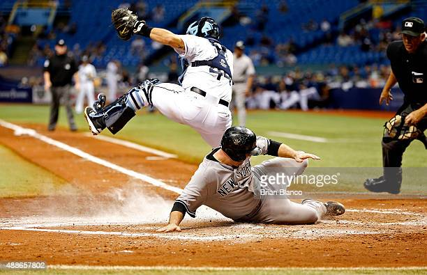 Brian McCann of the New York Yankees slides across home plate ahead of catcher Rene Rivera of the Tampa Bay Rays to score off of an RBI single by...