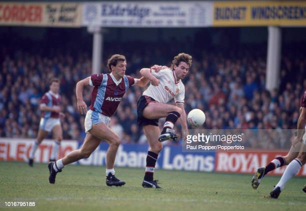 Brian McClair of Manchester United is challenged by Alvin Martin of West Ham United during a Barclays League Division One match at Upton Park on...