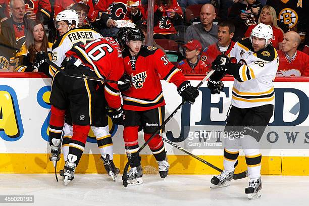 Brian McGrattan and Paul Byron of the Calgary Flames skates against Matt Fraser and Johnny Boychuk of the Boston Bruins at Scotiabank Saddledome on...