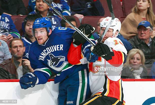 Brian McGrattan of the Calgary Flames and Yannick Weber of the Vancouver Canucks collide during their NHL game at Rogers Arena January 18 2014 in...