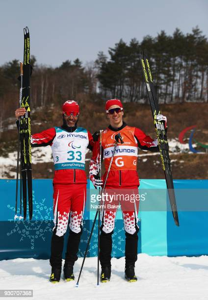 Brian McKeever and his guide Graham Nishikawa of Canada celebrate during the victory ceremony after winning the Gold Medal for the Men's 20km free...