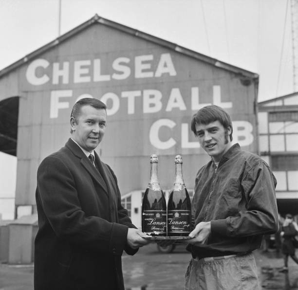 Brian Mears , chairman of Chelsea Football Club, holding two bottles of Lanson Champagne with English soccer player Ian Hutchinson , London, UK, 7th...