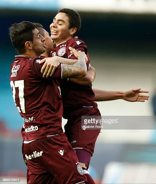 Brian Montenegro of Lanus celebrates with teammates Miguel Almiron and Roman Martinez after scoring the first goal of his team during a match between...