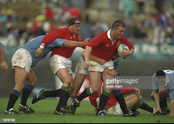 Brian Moore of the British Lions helps his team mate Richard Webster with the ball to escape the North Auckland player's clutches in the Lions v...
