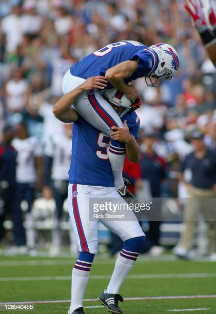 Brian Moorman of the Buffalo Bills celebrates with Rian Lindell after kicked the game winning fieldgoal against the New England Patriots at Ralph...