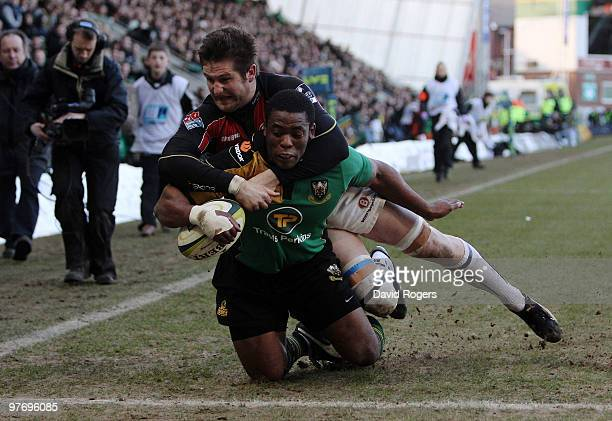 Brian Mujati of Northampton dives over to score a try despite being held by Ernst Joubert during the LV=Anglo Welsh Cup Semi Final between...