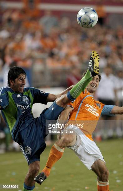 Brian Mullan of the Houston Dynamo avoids being kicked from Leo Gonzalez of the Seattle Sounders FC at Robertson Stadium on August 23 2009 in Houston...