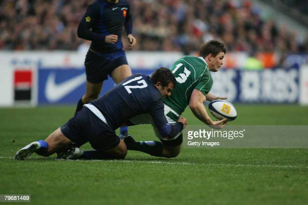 Brian O'Driscoll of Ireland offloads as he is tackled by Damien Traille of France during the RBS Six Nations Championship match between France and...