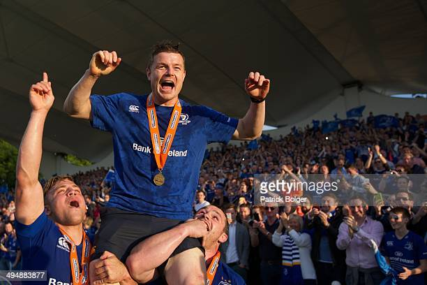 Brian O'Driscoll of Leinster in the last match of his career is carried by Ian Madigan and Cian Healy after winning the Pro 12 trophy after victory...