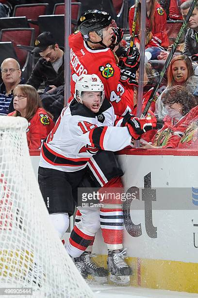 Brian O'Neill of the New Jersey Devils checks Viktor Svedberg of the Chicago Blackhawks into the boards in the second period of the NHL game at the...