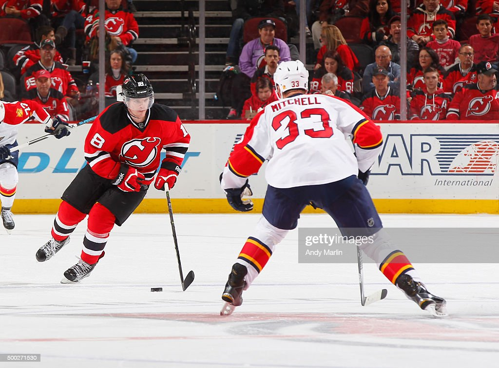 Brian O'Neill #18 of the New Jersey Devils plays the puck while being defended by Willie Mitchell #33 of the Florida Panthers at the Prudential Center on December 6, 2015 in Newark, New Jersey.