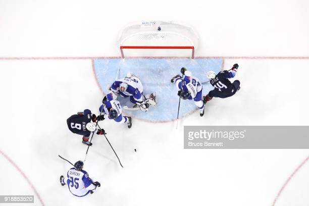 Brian O'Neill of the United States and Ivan Baranka of Slovakia battle for the puck during the Men's Ice Hockey Preliminary Round Group B game at...